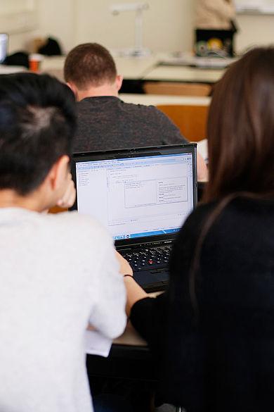 Zwei Studierende vor einem Computer